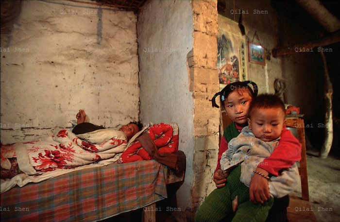 QSFeature02AIDS022 20020212 DONGGUAN, CHINA:  Flanked by his children (age 7 and 1) and his mother, 27 yr old AIDS paitient Ding Hongjun lays in his death bed in Dongguan Village, Henan Province, China 12 February 2002. Like Ding, over 700,000 peasant farmers have contracted the HIV virus when they participated in the unregulated blood selling/buying boom of the early and mid nineties. Ding died shortly after this photo was taken..Photo by: Qilai Shen...