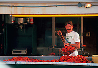A vendor sells boiled lobsters at a New England seafood restaurant. Essex, Massachusetts.