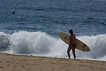 A surfer carries a surfboard on the beach of San Pancho Mexico.