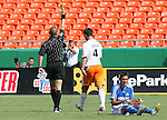 24 June 2007: Houston's Patrick Ianni (4) is shown the yellow card by referee Jozef Batko (l) in the 31st minute for fouling Kansas City's Davy Arnaud (r).  The Houston Dynamo defeated the Kansas City Wizards 1-0 at Arrowhead Stadium in Kansas City, Missouri in a regular season Major League Soccer 2007 game.