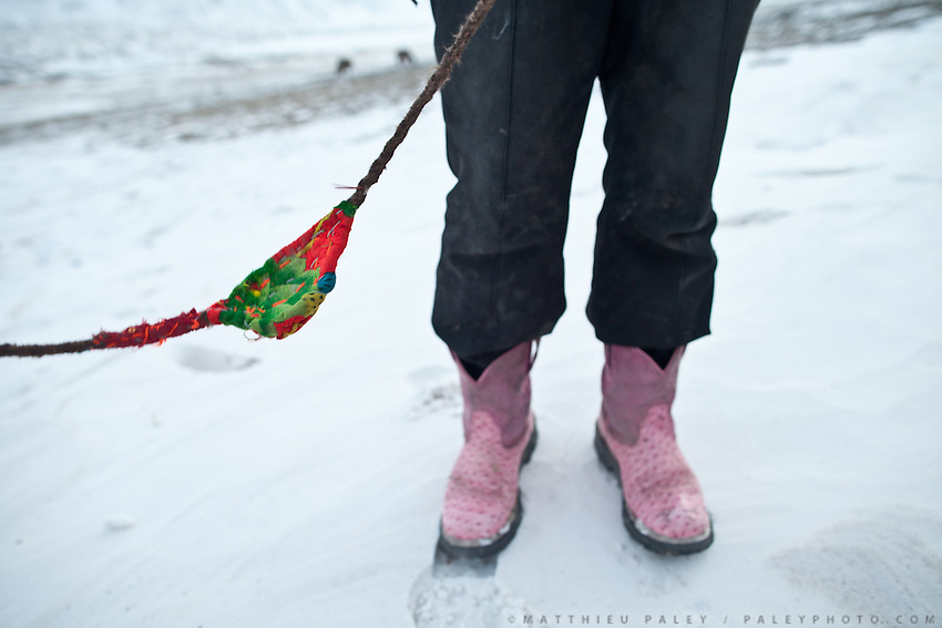Juma Boi,  his pink boots and a slingshot to round up yaks..In camp of Ech Keli (er Ali Boi's camp)...Trekking through the high altitude plateau of the Little Pamir mountains, where the Afghan Kyrgyz community live all year, on the borders of China, Tajikistan and Pakistan.