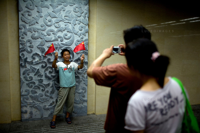 A Chinese Olympic team fan poses for a photo near Tian'anmen Square in Beijing, China on Sunday, August 10, 2008.  Kevin German