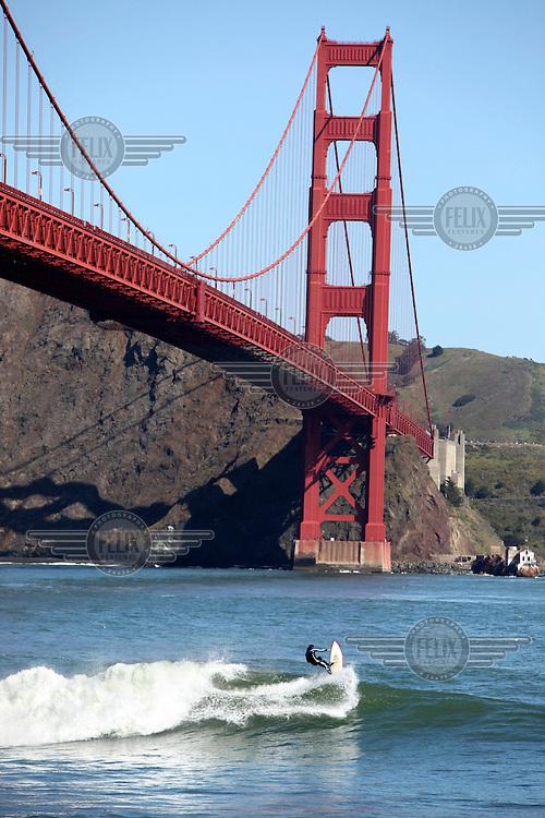A surfer in the San Francisco Bay at the Golden Gate Bridge, San Francisco, California.