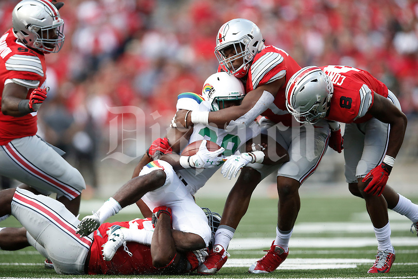 Ohio State Buckeyes defensive lineman Tyquan Lewis (59), on ground, and Ohio State Buckeyes linebacker Joshua Perry (37), standing, wrap up Hawaii Warriors running back Paul Harris (29) in the first half of an NCAA football game between the Ohio State Buckeyes and the University of Hawaii at Ohio Stadium in Columbus, Ohio, on Saturday, September 12, 2015. (Columbus Dispatch photo by Fred Squillante)