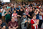 Home supporters applauding their team's victory from the Ealing Road terrace as Brentford hosted Leeds United in an EFL Championship match at Griffin Park. Formed in 1889, Brentford have played their home games at Griffin Park since 1904, but are moving to a new purpose-built stadium nearby. The home team won this match by 2-0 watched by a crowd of 11,580.