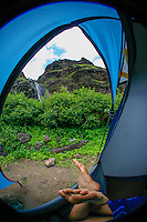 A woman's feet stick out of a blue camping tent, with a waterfall and lush surroundings in the background, Na Pali Coast, Kaua'i.