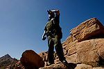 U.S. Border Patrol Agent Juan Munoz looks for illegal aliens in the rugged mountains near El Centro, Calif. on Tuesday, March 29, 2005.<br />