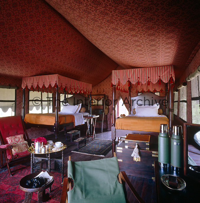 Each bedroom tent has four-poster beds with striped canopies trimmed in red velvet and tassels, carpets, chairs and side tables