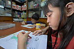 A girl colors a picture in Knox United Methodist Church in Manila, Philippines. The church offers food, showers, and fellowship to hungry people in its neighborhood. Included is an educational opportunity for children.