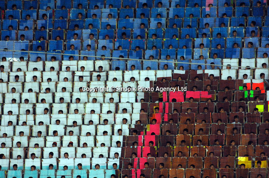 "Some of the 20,000 people who carry cards to make the huge pictures. The people have a series of pictures to make a series of huge pictures that act as a dramatic back-drop. The Arirang Games in PyongYang, North Korea. Over 100,000 perform. The Mass Games are government-organized events glorifying its two leaders of the DPRK (Democratic People's Republic of Korea) ""Dear Leader"", Kim Jong-il and his father the ""Great Leader"" Kim II-Sung."