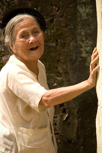 An older woman rests against a building in the small rural village of Tho Ha, just outside of Hanoi, Vietnam.