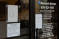 Signs advising patients hangs Friday, March 20, 2020, on the door at Monarch Dental at its location on Joyce Boulevard in Fayetteville. The Arkansas Department of Health and the Arkansas Dental Association recommends people reschedule non-emergency dental appointments in the wake of the covid-19 pandemic. Visit nwaonline.com/200322Daily/ for today's photo gallery.<br /> (NWA Democrat-Gazette/Andy Shupe)