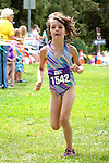 A young female competitor in the Chelanman Splash n Dash competition for little kids races to the finishline after swimming, biking and running the course.