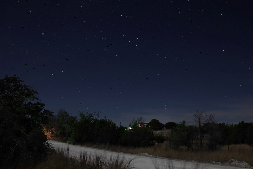 A cold December starry night with headlights approaching, and house lights on the hill..<br /> Central Texas Hill country.