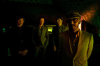 """Los Angeles, California, November 27, 2010 - A portrait of the band Ok Go, from left, guitarist/singer, Andy Ross (red), lead singer/guitarist, Damian Kulash (blue), drummer, Dan Konopka (green), and bass guitarist/singer, Tim Nordwind (yellow), .in the VIP lounge at the Nokia Club. OK Go was wrapping up a 16-month world tour by playing a song for Yo Gabba Gabba! during the day and later a final show at the Nokia Club. The Grammy Award-winning band has earned considerable fame for their creative, often low-budget music videos that are released on YouTube. Many have gone viral, including the 2006 video for """"Here It Goes Again"""", where the band performs a complex routine on treadmills. It has received over 50 million views to date. Kulash says the band left their major label and began their own to assert more creative control over their music and their videos. Adding, """"We're among the first musicians to view our YouTube videos as standalone artistic output, not advertisement for our recordings, and it shows in the numbers: over the past decade, we've sold a little over 600,000 records globally, and our videos have combined views in excess of 125 million.""""."""