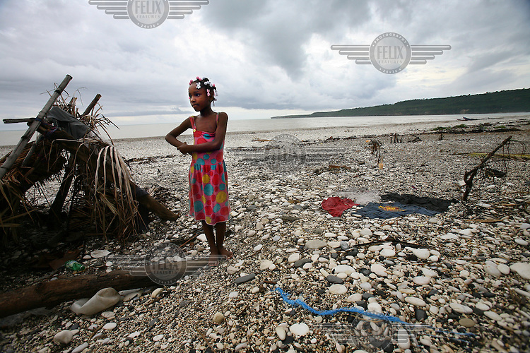 Kita Zedor stands on the waterfront in Bainet where over 20 homes and many people's livelihoods were washed away when Hurricane Dean hit the area 6 weeks ago.