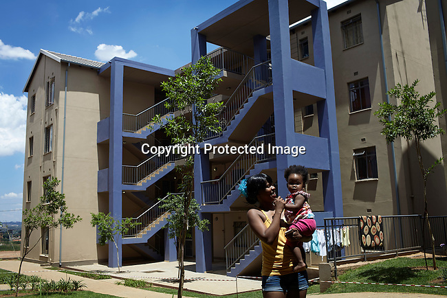 SOWETO, SOUTH AFRICA DECEMBER 17: Kgomotso Tshole and her 1 year old daughter stands outside the apartment block where they live on December 17, 2012 in Jabulani, section of Soweto, South Africa. Jabulani flats is one of the first apartment building developments in Soweto and local residents are just beginning learn how to live in an apartment. The residents of Soweto has seen massive investment such as shopping malls, parks, outdoor gyms in the township. Soweto today is a mix of old housing and newly constructed townhouses. The population in Soweto is estimated to be around one million people. A new hungry black middle-class is growing steadily. Many residents work in Johannesburg but the last years many shopping malls have been built, and people are starting to spend their money in Soweto (Photo by: Per-Anders Pettersson)