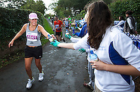 09 SEP 2011 - CHESTER, GBR - Janet Tate takes a bottle of water from one of the volunteers at the aid station in Churton during the MBNA Chester Marathon (PHOTO (C) NIGEL FARROW)
