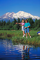 girl and boy with fishing poles along streamside with snow capped mountain in background. boy and girl. Mt. Shasta California USA.
