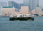 Hong Kong urban scene - Star Ferry moves across the bay in front of the Kowloon Ferry Terminal and the HK Concert Hall.