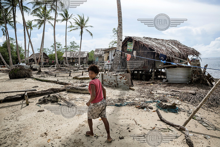 A woman walks through a village on the sea shore on Pamachau Island. Just 40 people live in nine houses on the island.