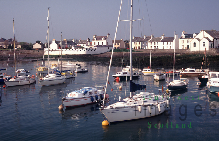 Isle of Whithorn yachts and fishing boats sitting along side harbour wall and moored in the bay in the Machars of Galloway Scotland UK