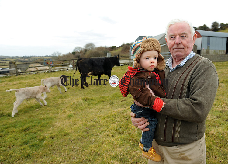 Sean Considiine of Cragmnagower with his ten month old grandson Jack tending to their cow which has had four sets of twins in a row over the last four years as well as two single calves before that. Photograph by John Kelly.