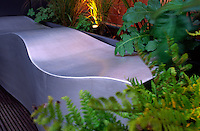 Cast stainless steel bench flanked by planted containers with lighting