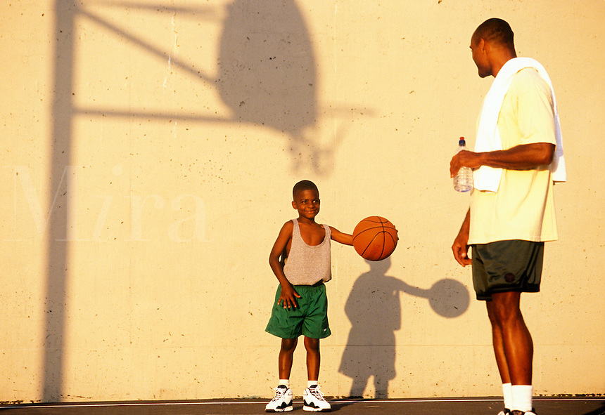 Boy looks up to adult basketball player with admiration.