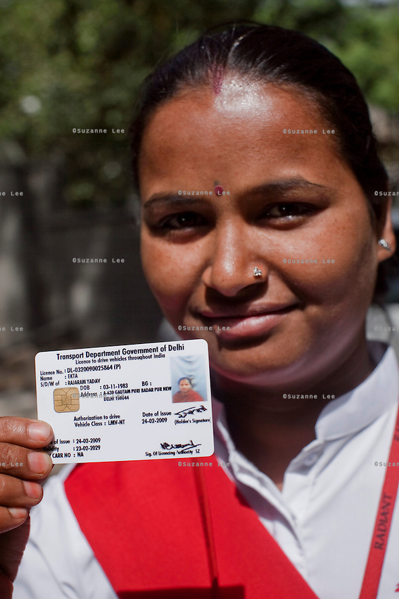 Ekta Yadav, aged 28, pose for a photo on 30th March 2010 with her driving licence, the only proof of identity she has.<br /> These female drivers were part of a program by Azad Foundation.<br /> Currently training their 4th batch of students, Azad Foundation was set up by Meenu Vadera (Executive Director) in New Delhi, India, to train Indian women in driving services. Upon completion, these women work as personal drivers for a period of time before they upgrade their driving licences to commercial licences, allowing them to drive taxis. With this program, Azad aims to empower Indian women including those previously abused or trafficked, while making Delhi a safer place for women travelling in public transport. Photo by Suzanne Lee for Panos London