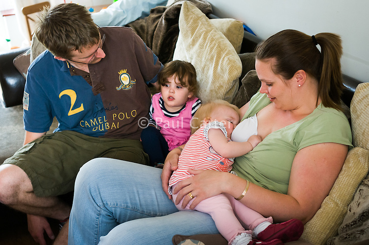 A mother breastfeeds her baby while sitting on a sofa watching television with her husband and young daughter.<br /> <br /> Taken: 01/05/2011<br /> Hampshire, England, UK