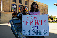 "Phoenix, Arizona. January 19, 2013 - A demonstrator hold a sign asking the federal government to go against criminals not guns owners. The rally to support gun rights took place in front of the historic Arizona Capitol. As President Barack Obama proposed new gun regulations last week, gun owners demonstrated against it with national ""Guns Across America"" rallies to defend the Second Amendment. Dozens showed up at the Arizona State Capitol, many of them carrying weapons. Photo by Eduardo Barraza © 2013"