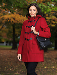Beautiful young woman wearing a red coat standing on a city street in autumn