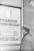 People read a bilingual poster of the German occupier, which is affixed to a wall.