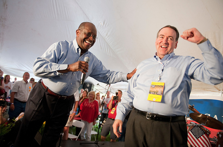 UNITED STATES - AUGUST 13:  Republican presidential candidate Herman Cain, left, and former Arkansas governor Mike Huckabee celebrate after performing a gospel song for supporters in Cain's tent at the Ames Straw Poll at the Iowa State University in Ames, Iowa.   (Photo By Tom Williams/Roll Call)