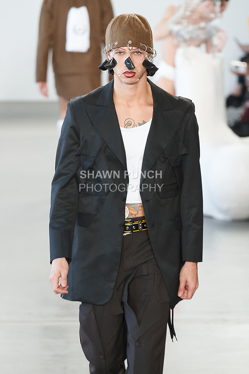 """Model walks runway in an outfit from the Sanchez-Kane Autumn Winter 2018 """"Artesanal Sex Shop"""" collection by Barbara Sanchez Kane, at Pier59 Studios in New York City, on February 5, 2018; during New York Fashion Week: Men's Fall Winter 2018."""