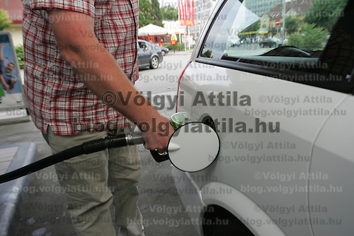 Male driver fuels up her car at a gas station in Budapest, Hungary on June 10, 2009. ATTILA VOLGYI