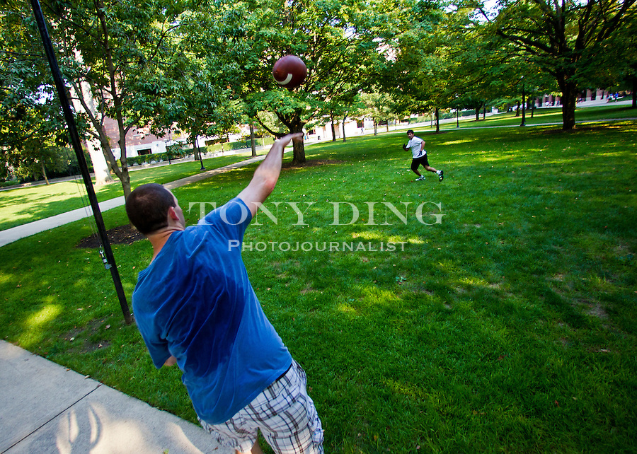Sophomore mechanical engineering student Josh Muss of Omaha, Neb. throws a football to biomedical engineering junior Anu Balijepalli of Midland, Mich., on the University of Michigan's Diag, Friday, Sept. 2, 2011 in Ann Arbor, Mich. (Tony Ding for The New York Times)