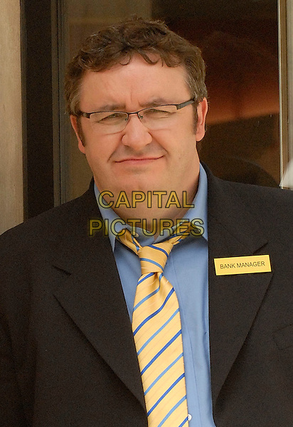 MARK BENTON.During filming of the new Nationwide Building Society Advert, in which he reprises his role as the annoying, smug bank manager..Holbon, London, England, .2nd August 2008..half length portrait  advertising TV yellow tie glasses suit jacket .CAP/IA.©Ian Allis/Capital Pictures