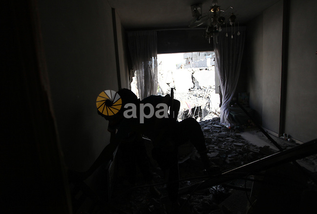 Palestinians inspect the remains of house, which witnesses said was hit by an Israeli air strike in Gaza city August 9, 2014. Israel launched more than 20 aerial attacks in Gaza early on Saturday and militants fired several rockets at Israel in a second day of violence since a failure to extend an Egyptian-mediated truce that halted a monthlong war earlier this week. The Israeli military said that since midnight it had attacked more than 20 sites in the coastal enclave where Hamas Islamists are dominant, without specifying the targets. Medical officials in Gaza said two Palestinians were killed when their motorcycle was bombed and the bodies of three others were found beneath the rubble of one of three bombed mosques. The air strikes which lasted through the night also bombed three houses, and fighter planes also strafed open areas, medical officials said. Photo by Ashraf Amra