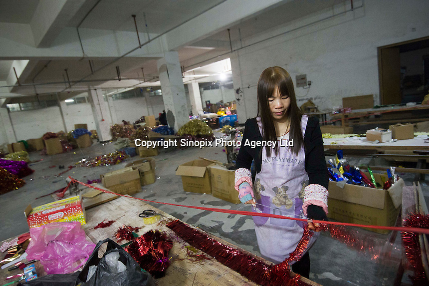 November 28, 2015, Yiwu, China - A female migrant worker measures strips of tinesel by hand at the Xin Shua tinsel factory. The factory makes around 30 million RMB (GPB 3.12) of tinsel each year.Photo by Dave Tacon / Sinopix