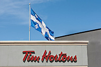 A Quebec Flag flies over A Tim Hortons coffee shop in Levis, just South of Quebec City August 27, 2010. Tim Hortons Inc. is a Canadian coffee shop known for its coffee and doughnuts.