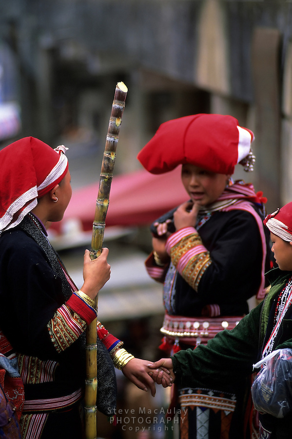 Red Dao/Zao hilltribe women and child in the vibrant and detailed traditional garb they wear daily, Sapa, Northern Vietnam.