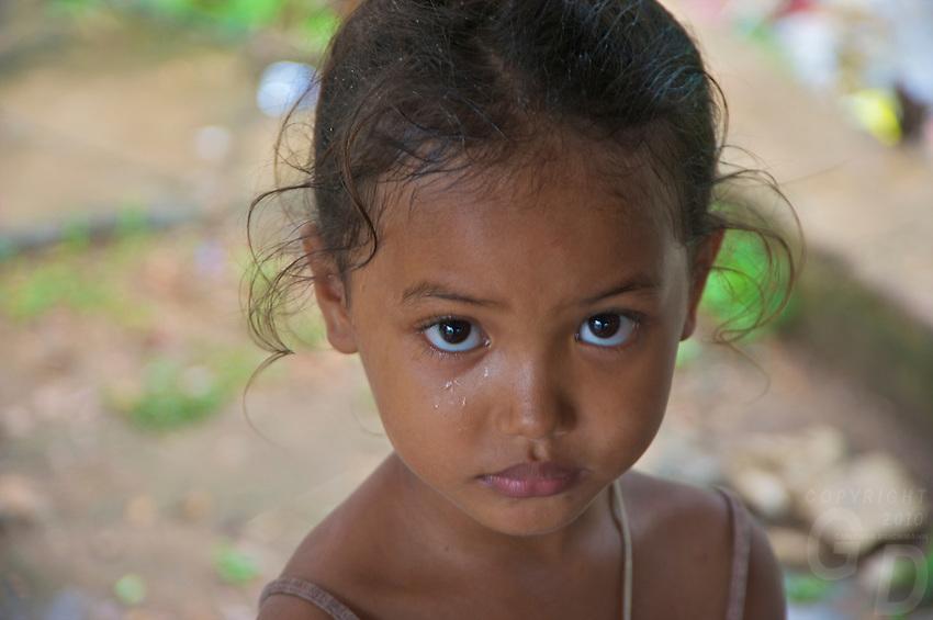 Portrait of a little girl during a tropical rain shower rural area near Battambang Cambodia