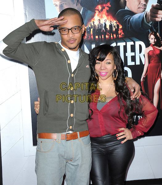 "T.I. (T.I.P.) (Clifford Joseph Harris, Jr.) & Tiny (Tameka Cottle).""Gangster Squad"" Los Angeles Premiere held at Grauman's Chinese Theatre, Hollywood, California, USA.     .January 7th, 2013.half length grey gray cardigan glasses red top hand on hip married husband wife arm over shoulder salute .CAP/DVS.©DVS/Capital Pictures."