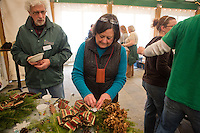 Friends of the Wissahickon Trail Ambassador Don Simon talks watches as Suzanne Zimmermann afixes a snowflake to her wreath at the Winter in the Wissahickon event hosted by the Friends of the Wissahickon on December 1. (Dave Tavani/for NewsWorks)
