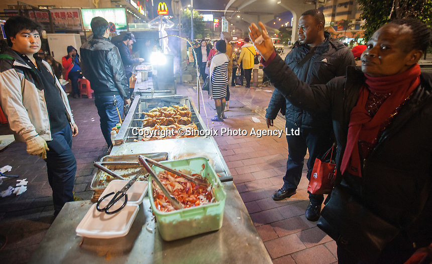 African and Chinese people are seen by a Uighur food stall in an area of Guangzhou known to locals as 'Chocolate City', Guangzhou, Guangdong Province, China, 08 December 2014. The health authorities of Guangzhou are said to be stepping up their monitoring of the African community in light of the ongoing outbreak of the Ebola virus disease in West Africa.