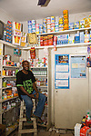 A proprietary patent medicine vendor (PPMV) in the Dakata area of Kano, Nigeria, display Gold Circle and Lifestyles condoms, Waterguard - a chlorine product that makes water safe to drink - and malaria treatment drugs on it shelves. These products are distributed by the Society for Family Health (SFH), Nigeria's largest indigenous non-profit and affiliate of the international social marketing organization, Population Services International (PSI).  To the right of the shopkeeper is a malaria treatment job aid developed and produced by SFH, with USAID funding.