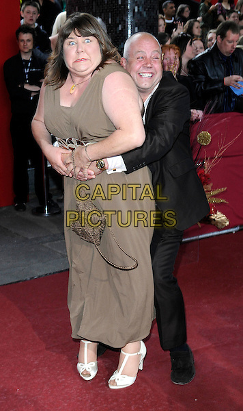 CHERYL FERGISON & CLIFF PARISI.Arrivals - the British Soap Awards 2009, BBC Television Centre, Wood Lane, London, England..May 9th 2009.soaps tv full length Eastenders green brown khaki dress long maxi suit arms around waist hug embrace funny ferguson.CAP/FIN.©Steve Finn/Capital Pictures.
