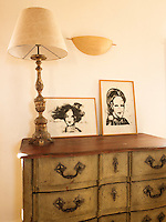 A pair of pen and ink drawings on top of an antique chest of drawers in the bedroom
